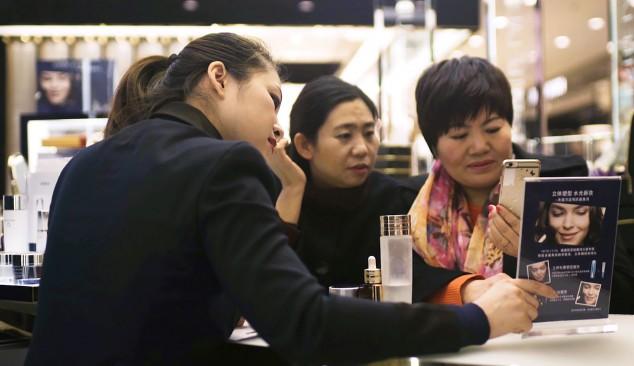Китайские покупатели знакомятся с промо акцией, которую проводит Alibaba в магазине Estée Lauder