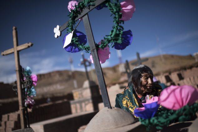 Женщина возлагает цветы на главном кладбище Сускеса